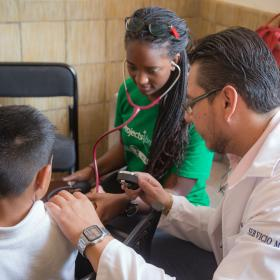 A student on a spring break project in Mexico checks a child's pressure during a Public Health outreach.